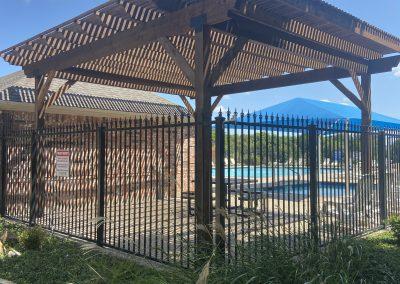 iron fence around wooden pergola