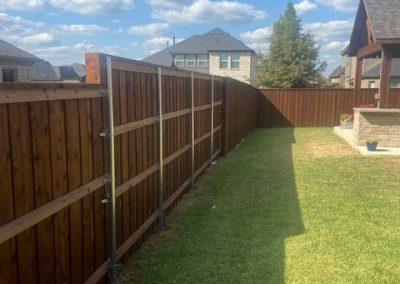 Prestained board-on-board western red cedar wood fence with 2x4 treated rails